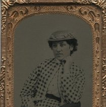 Image of Woman wearing hat and checkered outfit -