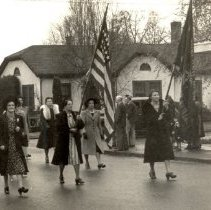 Image of Legion Auxillary Parade.  Mrs. Lang with flag, Leona Miller left edge, Mrs. Moon under arch of flag - 2016FIC2620