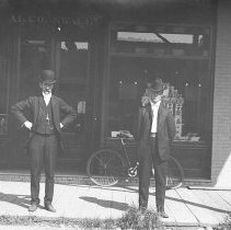 Image of Two men outside A.L. Cornwall Drug and Variety Store 487 Front Street - 2015FIC1044
