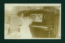 Image of Woman and Baby in Front of a Piano.