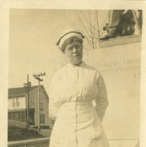 Image of 2010.02 - Nurse Cora Gottreau standing in white nurses' uniform outside with Charles E. Still's home in background