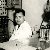 Image of 2010.02 - F.T. Dun wearing white lab coat seated in front of table and medical machine