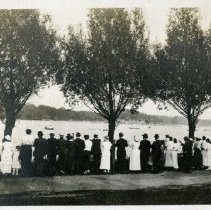 Image of 2010.87 - Photograph of crowd standing along shore watching boat races