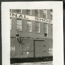 Image of 2011.86 - Photograph of Man on Railroad Car in Front of International Shoe Company