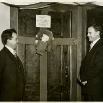 Image of 1983.829 - George E. Snyder and Pressley L. Crummy in front of door wrapped as Christmas present 1949