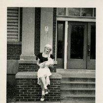 Image of 1983.829 - David T. Garland Jr. in drag sitting on stair landing during Sadie Hawkins 1948