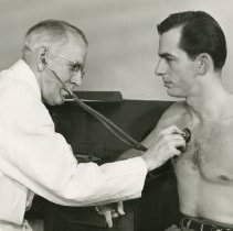 Image of W. Neil Johnstone applying stethoscope to patient
