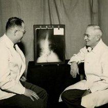 Image of 1985.1050 - James Keller & Wallace Pearson examining x-ray of abdomen