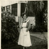 Image of 1991.1277 - Galli Curci in white apron holding farm tool