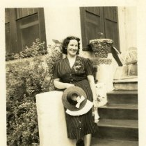 Image of 2006.46 - Lucilee Johnson in striped dress holding hat on steps