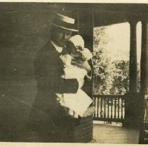 Image of 1984.978 - George M. Laughlin holding Mary Jane Laughlin with unidentified woman on porch