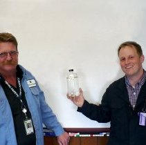 Image of Coby Stewart & Brian Carlson with first bottle of Monroe Energy jet fuel