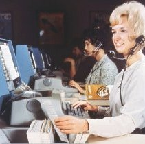 Image of Delta Reservations Agent with OAG at her right, mid 1960s