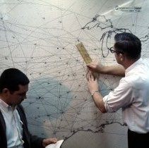 Image of Northwest Airlines Chief Meteorologist Dan Sowa using wall map, 1950s