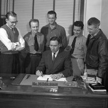 Image of C.E. Woolman signing Veterans Training contract, 1940s.