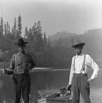 Image of GP4/5.355 - COUNT:I  REMARKS:Walt Cowan on left holding fishing pole upright; George Applegate on right, holding rope to boat in the Umpqua River at Scottsburg, OR. Both men of Yoncalla, OR. Background shows river, timbered hills and river bank. Peret photo, CA 1920