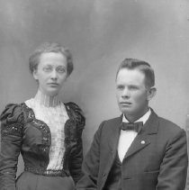 Image of GP4/5.496 - REMARKS:Studio portrait of a young woman and a young man. He is wearing a suit and she wears a dress with the jacket trimmed in lace and beads.
