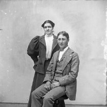 Image of GP4/5.498 - REMARKS:Studio portrait of a young couple. He wears a three-piece suit; she wears a suit with huge puffed sleeves and two large buttons.