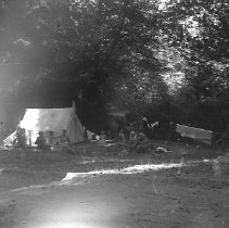 Image of GP4/5.53 - REMARKS:A number of adults and children camped out. A tent with an American flag on top and a wagon to the right. Same as GP4/5.54