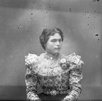 Image of GP4/5.655 - REMARKS:Studio portrait of a young girl in a ruffled blouse with a bouquet of flowers on her shoulder.  OBJECT DATE:ca. 1890