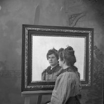 Image of GP4/5.669 - REMARKS:Studio portrait of a young girl sitting with her back to the camera and gazing at her image in a mirror.