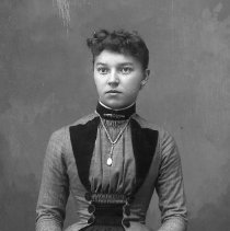 Image of GP4/5.791 - REMARKS:Studio portrait of a young woman in a plaid dress with a plain overskirt and holding a rose in her hand.  OBJECT DATE:ca. 1890's