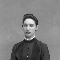 Image of GP4/5.840 - REMARKS:Studio portrait of a young woman wearing earrings and a dress with tight sleeves, double lapels and a row of buttons down the front.  OBJECT DATE:ca 1890's