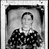 Image of GP4/5.18 - REMARKS:Young woman in flower brocade dress, plaid belt, mitts, tassells hanging from hair net? earrings; copy of early photo
