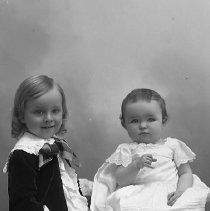 Image of GP5/7.1095 - REMARKS:Studio portrait of two small children. Older child wears a dress with plaid skirt; baby wears lace trimmed dress. (See GP5/7.1096)  OBJECT DATE:ca. 1890