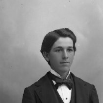 Image of GP5/7.1169 - REMARKS:Studio portrait of a young man dressed in a formal suit, bow tie and tucked shirt front with a stud. His watch chain has three strands held in the center with a square clasp.  OBJECT DATE:ca. 1890