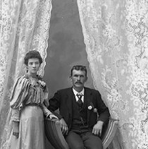 Image of GP5/7.1205 - REMARKS:Studio portrait of young couple; appears to be a wedding photo. She wears a corsage and he has a flower in his lapel.