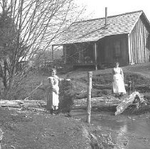 Image of GP5/7.344 - REMARKS:Mollie Hamilton house, Glendale, OR, ca 1910. Board and batten house. Two women shown, beside nearby creek.  OBJECT DATE:ca 1910