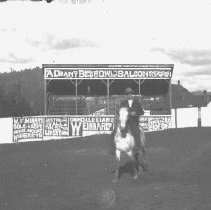 """Image of GP5/7.372 - REMARKS:Rodeo scene; shows rider on horse, bleachers, fence with many posters, including ad for """"Albany Beerowl Saloon"""". Glendale,OR area, ca 1910.  OBJECT DATE:ca 1910"""