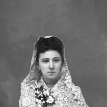 Image of GP5/7.464 - Studio portrait of a young girl wearing a lace mantilla shawl on her head and a corsage.  OBJECT DATE:ca. 1890