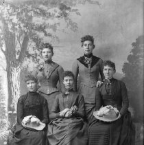 Image of GP5/7.586 - REMARKS:Studio portrait of five young women all wearing very elaborate gowns trimmed with beads, ribbons and lace. All have corsages and ornate straw hats. All wear their hair in the pompadour hair style.  OBJECT DATE:ca. 1890