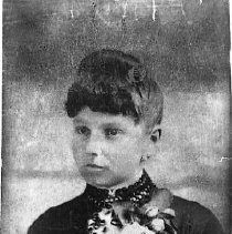 Image of GP5/7.655 - REMARKS:Studio portrait of a picture card. Photo shows a young woman wearing a dress with elaborate braid work, a rose corsage and a comb in her hair. (See GP5/7.656)  OBJECT DATE:ca. 1890