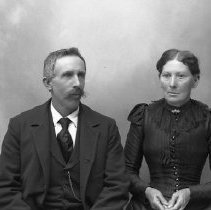 Image of GP5/7.668 - REMARKS:Studio portrait of an older couple. He has wide tie and long watch chain; she wears a dress with lace collar and small buttons.