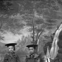 Image of GP5/7.852 - REMARKS:Studio portrait of two young boys dressed in costume. Both wear overalls; one a striped shirt and the other a polka dot shirt. They have flat hats. One has a toy drum; the other has a toy rifle and there is a small American flag and a toy sword next to them.  OBJECT DATE:ca. 1890