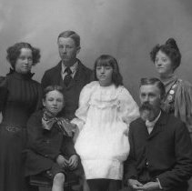 Image of GP5/7.878 - REMARKS:Studio portrait of a family. Father has short beard and moustache. Mother and daughters wear dresses with large leg-o-mutton sleeves.  OBJECT DATE:ca. 1890