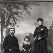 Image of GP5/7.957 - REMARKS:Studio portrait of a family. Man wears a suit with striped pants and holds a large brimmed felt hat. Woman wears a long dress with wide bands of ribbons on waist and skirt hem. Child has a dress with very wide lace collar.