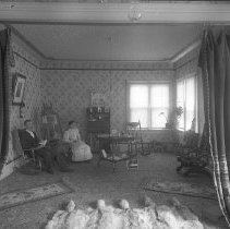 Image of GP8/10.105 - REMARKS:View of a small living room with many Victorian era touches: two wooden rocking chairs, a patent rocker, landscape painting on elaborate easel, wallpapered walls and ceiling, patterned carpet with small rugs, including a fur rug, on top of it. Man and woman are sitting in the room.