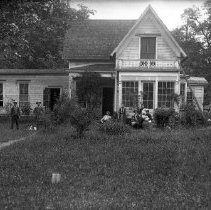 Image of GP8/10.108 - REMARKS:Substantial two-story house with many windows; it has a more primitive one-story extension on the back. There is a large group of people - men, women, small children - posing in front of it.