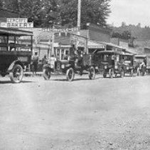 """Image of N10041 - REMARKS:A line-up of traffic in Canyonville, Oregon, when the Pacific Highway was being built. The first building, left rear, has a sign reading, """"Gem Cafe and Bakery."""" This was run by the Knott Family (also known as the Knott's Bakery. The barber shop at right of the cafe was operated by Bob couglasr, then next to the grocery and fountain, called the """"Oasis,"""" operated by George Carter.  INSCRIPTION:A sign reading, """"Gem Cafe and Bakery"""""""