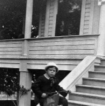 Image of N10074 - REMARKS:Dr. Hall Seely on a three-wheeled tricycle at the staps to a wooden house. The photo was taken when he was about five or six years old.