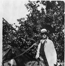Image of N10507 - REMARKS:Man with white linen duster on horseback, reportedly George Zimmerman.