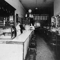 Image of N10895 - REMARKS:Interior of a Roseburg Confectionery; fountain at left candy cases at right. View shows two women and one man, ca. 1910. (Building has electric lights)  OBJECT DATE:ca. 1910