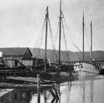 Image of N11378 - REMARKS:The Coos Bay, Roseburg and Eastern RR and Navigation Co. locomotive shunts a mixed train on the docis at Marshfield, Oregon. Both sailing and steam schooners lie alongside to discharge cargo and load lumber.