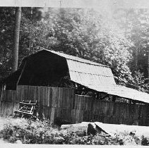 Image of N11454B - REMARKS:The George W. Collins Homestead Claim. This photo shows an unusual barn with long sheds on both sides.
