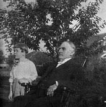 Image of N11509 - REMARKS:Binger Hermann seated in rocking chair with great grandson standing by his side.