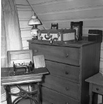 Image of N11650 - REMARKS:Interior view of the Lily Moore home, Roseburg, Or., showing a chest of drawers, sewing machine in a second story room.